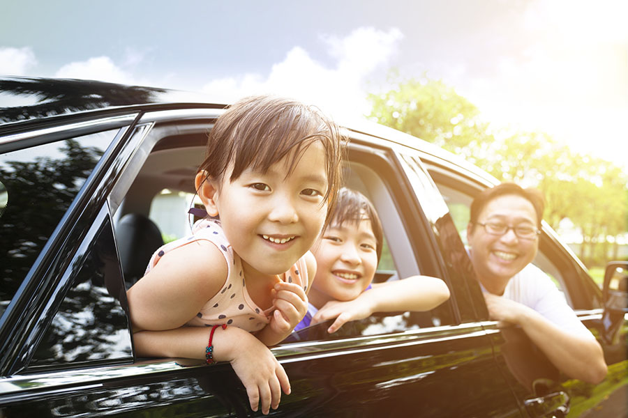 Personal Insurance - Happy Family Sitting In Car Looking Out Window